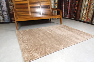 A 4 feet by 6 feet rug in brown.