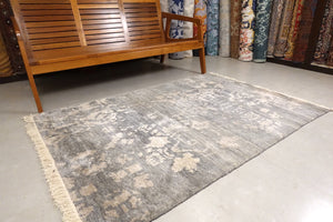 This 4 feet by 6 feet rug is an abstract floral design with pastel shades. The colours are gray and white.