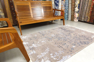 This rug is 4 feet by 6 feet in size and is an erased design based on the art nouveau style. The colours are a very pastel purple, with darker purple and light purple on the design.