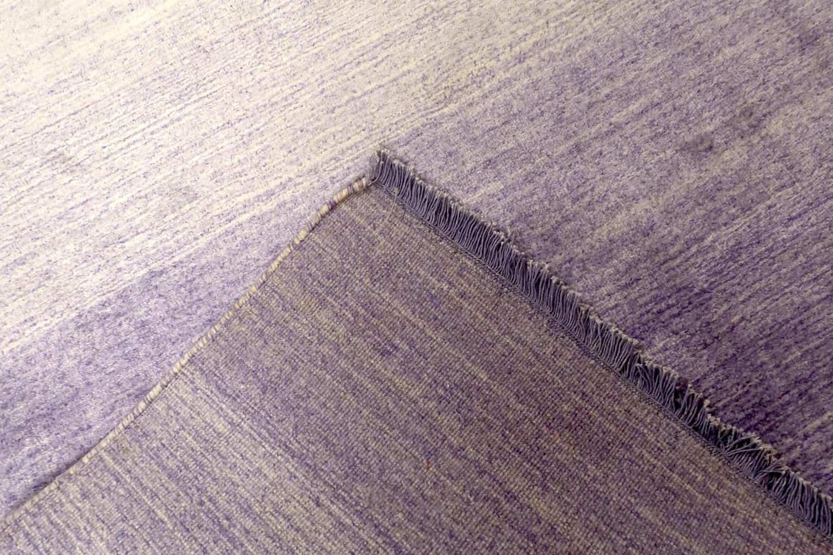 A 4.5 feet by 8 feet rug that is purple and fades inwards with white.