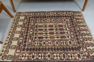 A 3.8 feet by 5 feet wool kilim, the colours used on the rug are blue, beige, brown and tan.