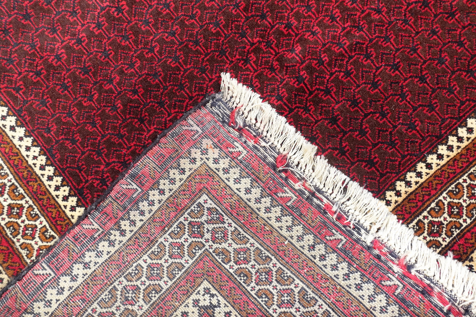 It is an Afghan wool rug that measures 3 feet 9 inches by 6 feet 4 inches. The colours used on the rug are red,beige and rust.