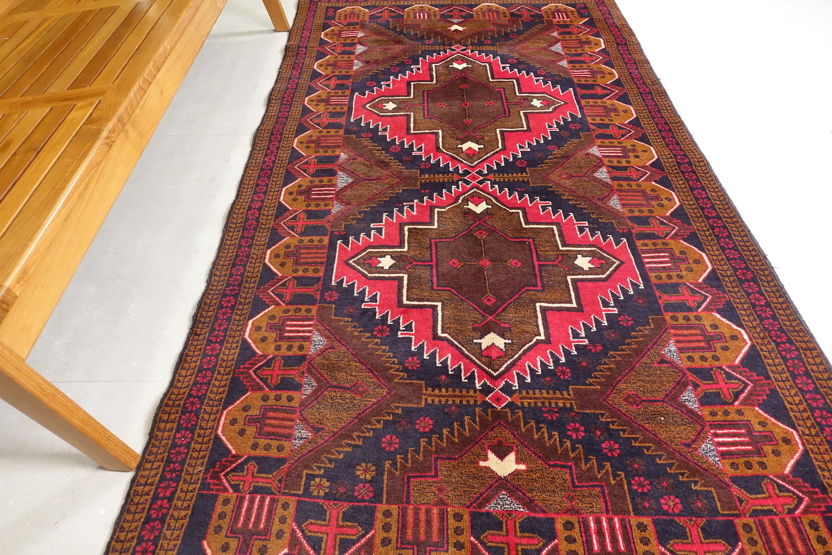 A 4 feet by 7.5 feet Balochi wool rug, the colours used are red, orange and blue.
