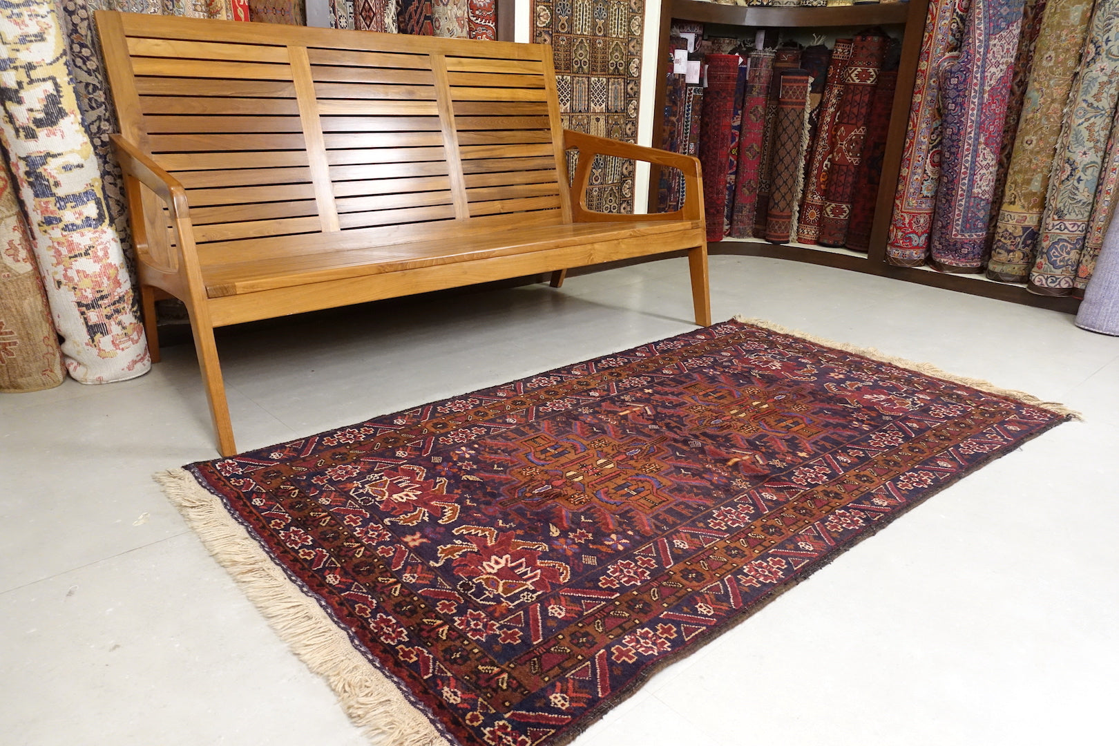 It is a 3.5 feet by 6 feet Afghan wool rug. The colours used are dark blue, brick red and rust.