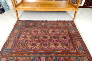 A 4 by 5.5 feet afghan wool rug. The main colours include blues, green, orange-red and tan.