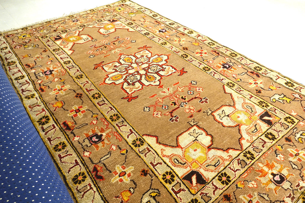 It is a 4 feet by 7 feet Indian wool rug. The colours of rust, beige, black and brick red are used on the rug.
