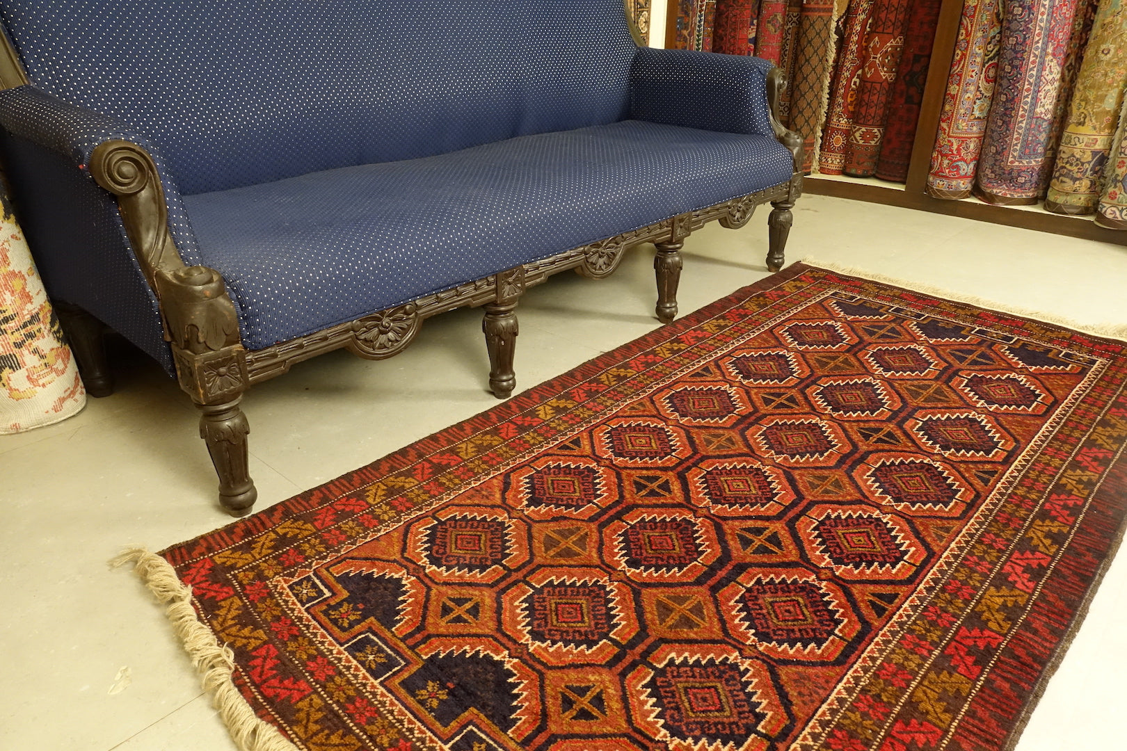 A 3.5 by 6 feet balochi wool carpet, the colours used on the rug are navy blue, orange and pink-red.