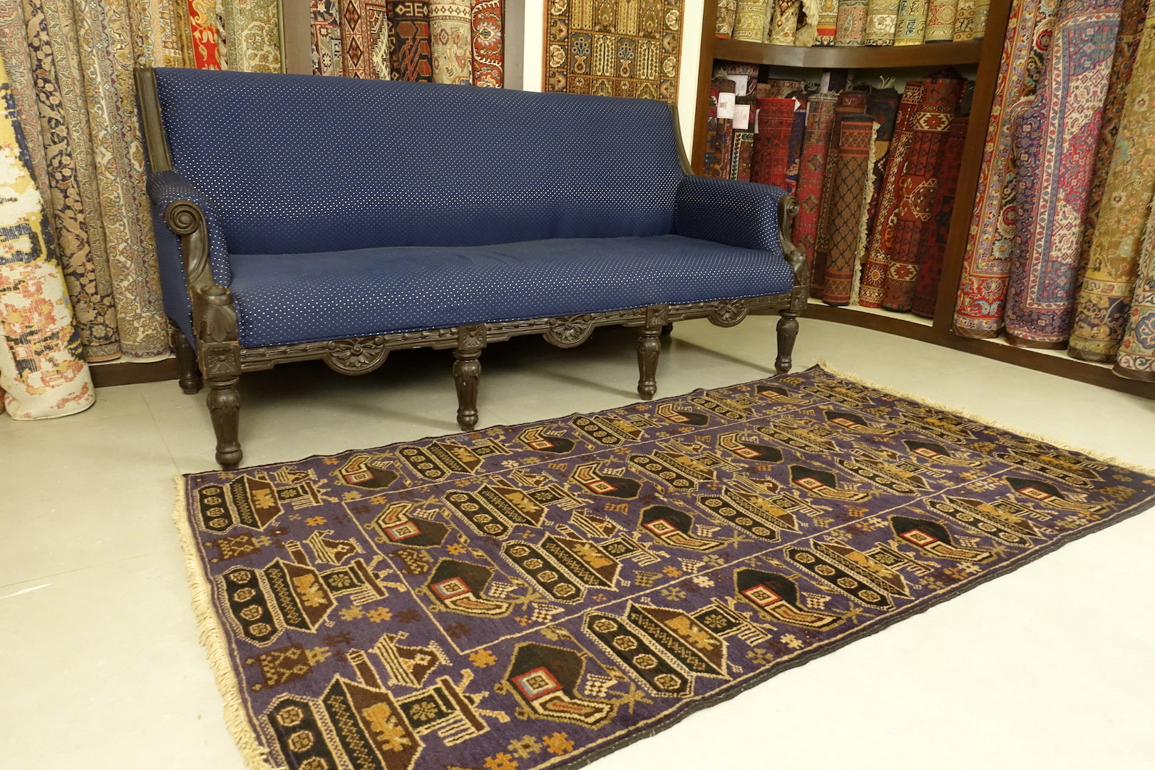 A balochi wool rug that measures 3.5 feet by 6 feet. The colours used on the rug are blue, orange, beige and rust.