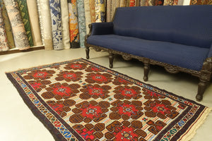 This Afghan wool rug measures 3 feet 9 inches by 6 feet 6 inches. The colours used on the rug are teal, red and beige.