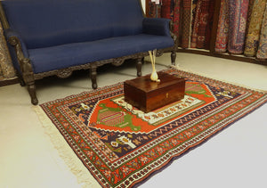 A 4 feet by 6 feet balochi wool rug, the colours used on the rug are red, green and beige.