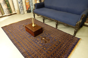 A 4 by 7 feet afghan wool rug. The colours used are typically blue, brown, beige and tan.