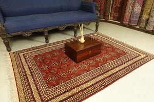 A 4 by 6 feet afghani wool rug. The colours used on the carpet are red, tan, deep blue and beige.