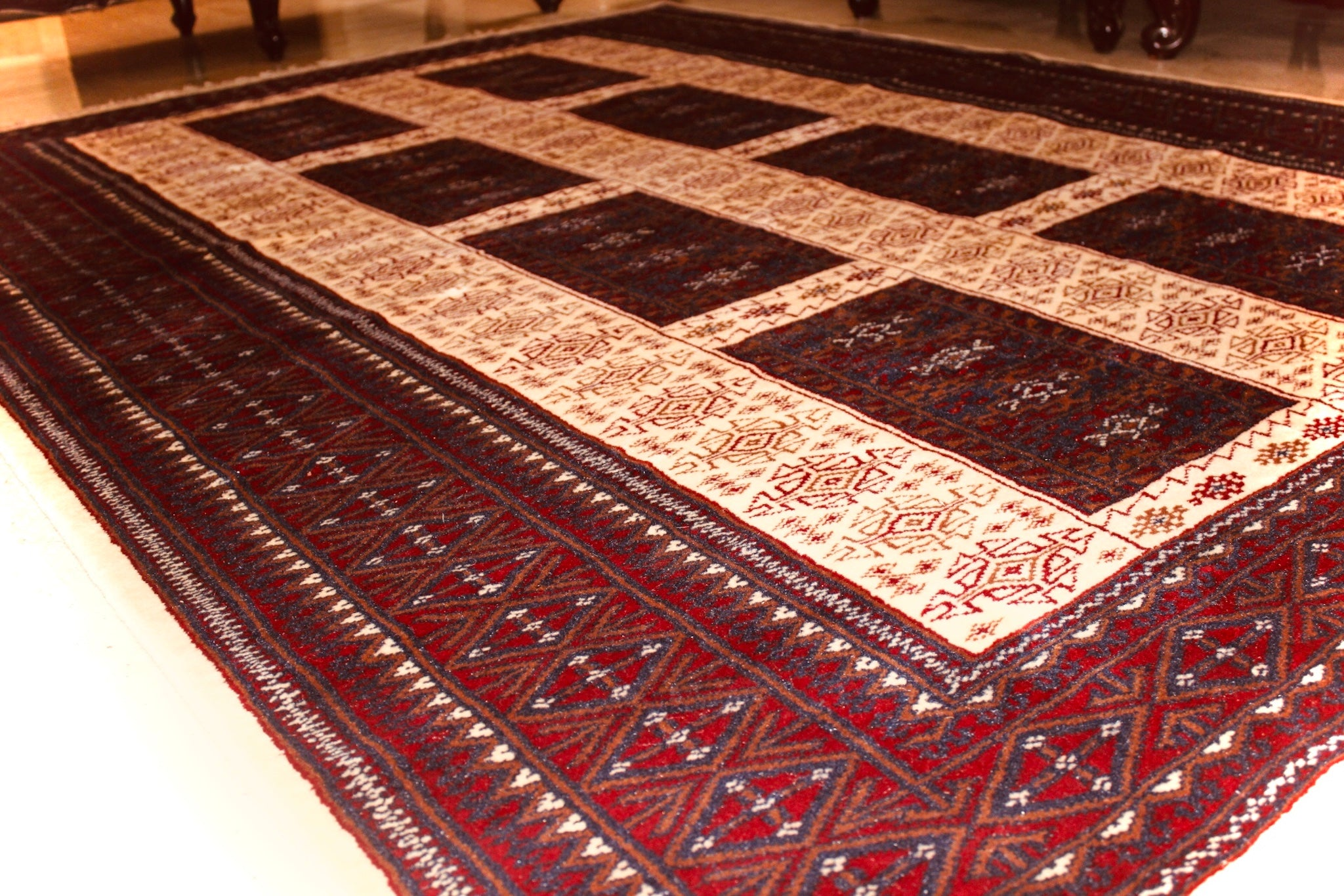A 5 feet by 7 feet indian wool rug, the colours used are deep red, rust, blue and white.