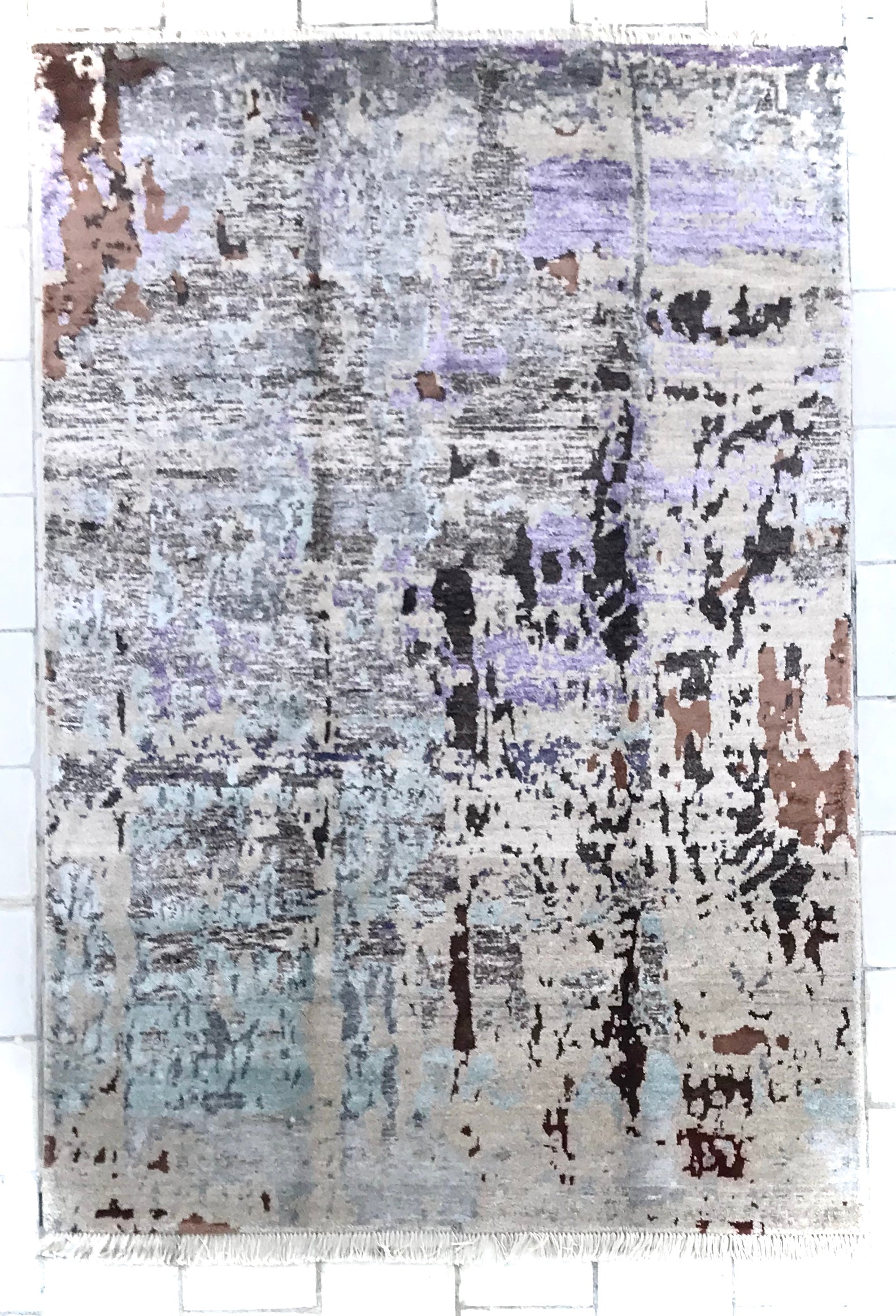 A modern rug/carpet with an abstract design. The rug is made of pastel colours. Creams, Blacks, Sea Blue and Sprinkles of brown and black. The size of the rug is 5 feet by 8 feet.