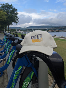Hat is outside on a bicycle with mountains and river and bridge in background.Logo is Locomotive black over gold.