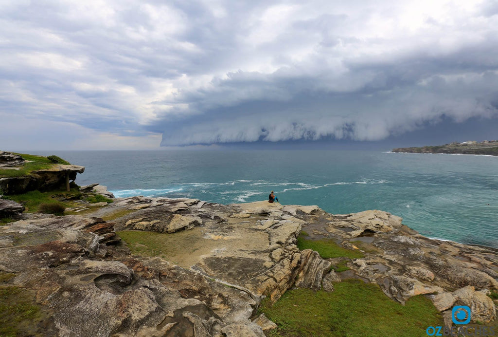 Girl sitting at Tamarama Beach watching a supercell storm approach