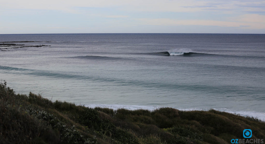 Sleek swell lines rolling into The Bommie at Ulladulla NSW on a smooth day