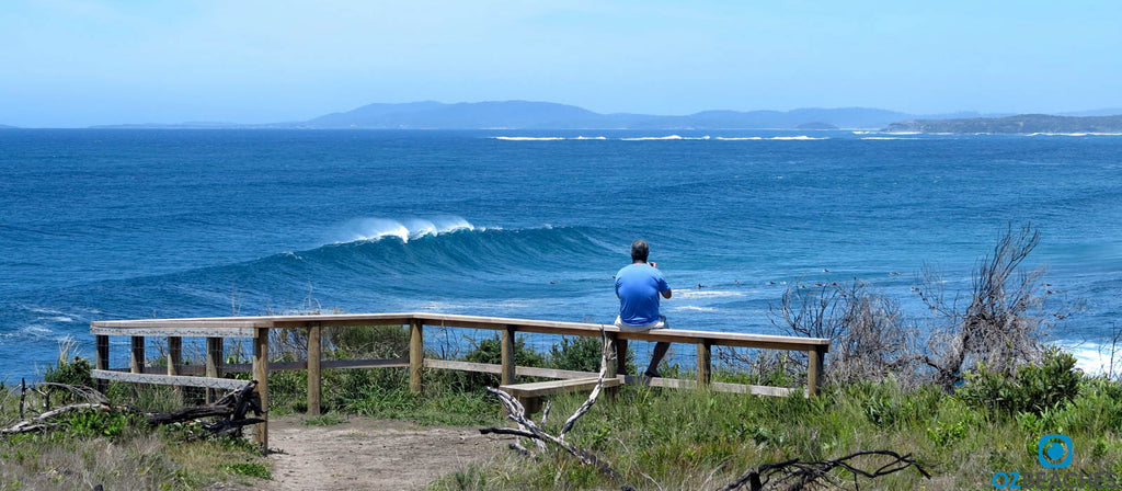 Huge wave rolls into The Bommie at Ulladulla NSW while a photographer watches on