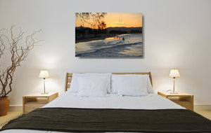 An acrylic print of a nice sunset at Belongil Beach, Byron Bay NSW hanging in a bed room setting