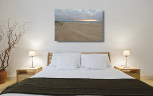 An acrylic print of a fisherman at sunrise at Blacksmiths Beach NSW hanging in a bed room setting
