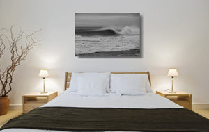 An acrylic print of a wave breaking at Sandon Point NSW hanging in a bed room setting