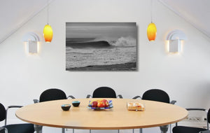 An acrylic print of a wave breaking at Sandon Point NSW hanging in a dining room setting