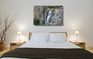 An acrylic print of Minyon Falls in NSW hanging in a bed room setting
