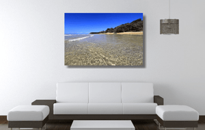An acrylic print of the crystal clear waters of Cylinder Beach on North Stradbroke Island QLD hanging in a lounge room setting
