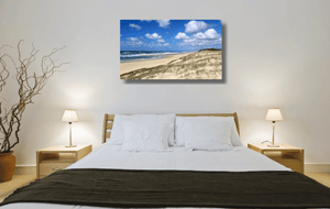 An acrylic print of Main Beach at Point Lookout on North Stradbroke Island QLD hanging in a bed room setting