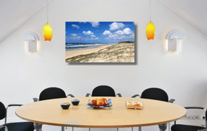 An acrylic print of Main Beach at Point Lookout on North Stradbroke Island QLD hanging in a dining room setting