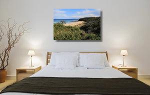 An acrylic print of Rennies Beach in Ulladulla NSW hanging in a bed room setting