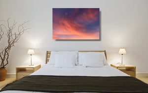 An acrylic print of a soft pastel sunset at Paradise Point QLD in hanging in a bed room setting