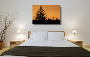 An acrylic print of the Sydney city skyline at sunset in hanging in a bed room setting