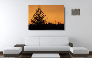 An acrylic print of the Sydney city skyline at sunset in hanging in a lounge room setting
