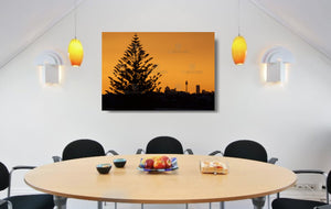 An acrylic print of the Sydney city skyline at sunset in hanging in a dining room setting