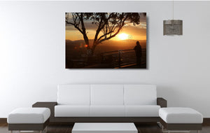 An acrylic print of a lone person standing at a lookout in Tamworth at sunset in hanging in a lounge room setting