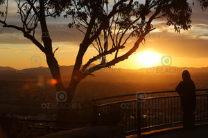 A photograph of a lone person watching the sunset from a lookout at Tamworth in NSW.