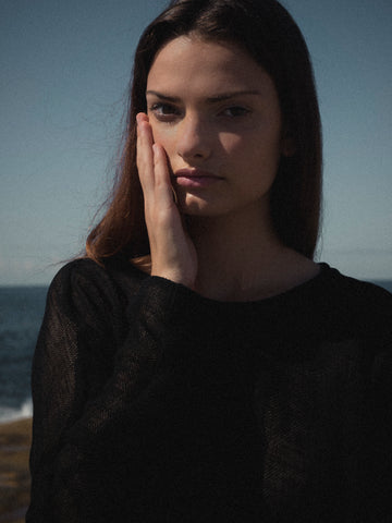 Model is holding her hand on her face
