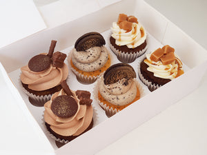A box of mixed flavoured cupcakes including Oreo cookie, chocolate, caramel and Biscoff flavours