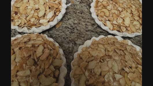4  apple pies without a tope crust.  We can see all of the lovely juicy apple slices that fill the bottom crusts