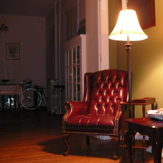 A bell shade floor lamp over a comfortable chair
