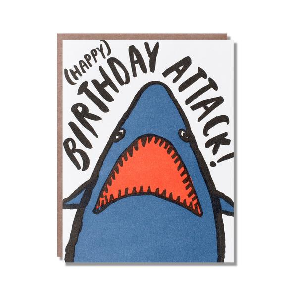 blue shark head with an open mouth. above of it '(happy) birthday attack!' written