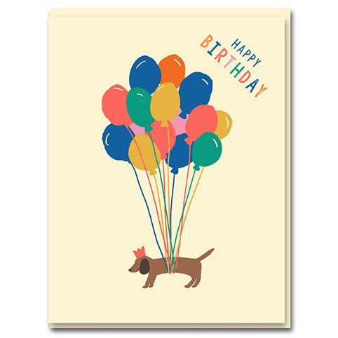 sausage dog is levitated by colourful balloons. 'happy birthday' written on the top corner.  base baby pink