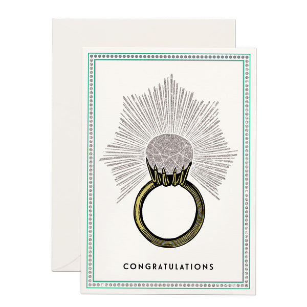 a huge engagement ring , 'congratulations' written at the bottom. base white