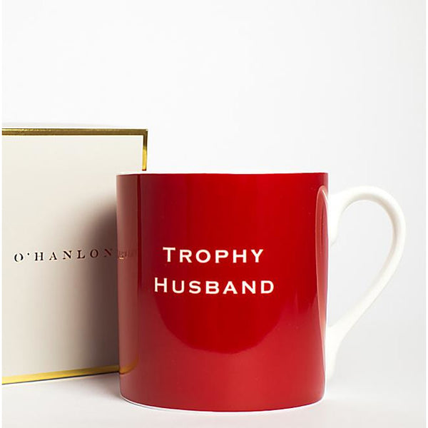 red mug, 'trophy husband' written on it.