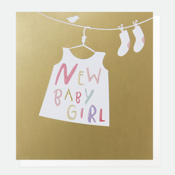 'new baby girl' written on the skirt hanged on laundry holder. base gold