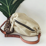 Pale yellow goat skin leather scrunchie belt or shoulder bag made by artisans in Haiti through educational programs providing generational change with fair wages and self-independence