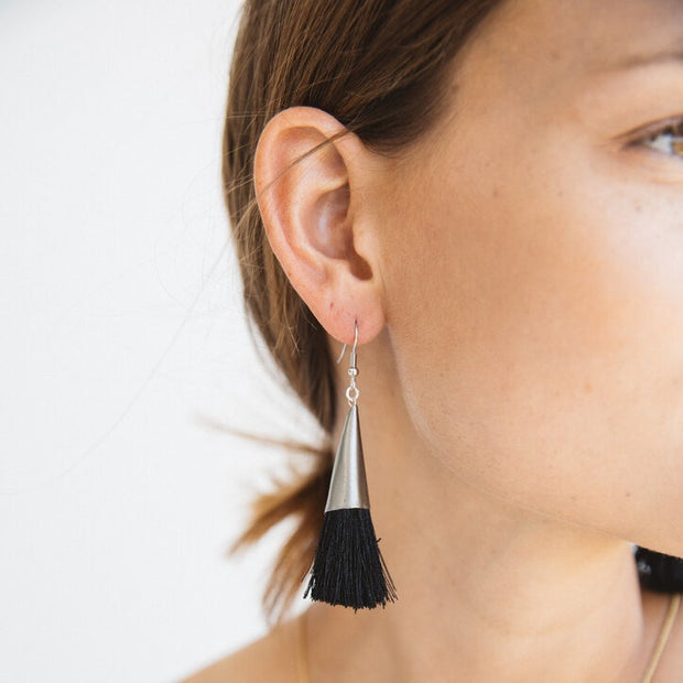 Recycled steel and black tassel earrings handmade by artisans in Haiti that are trained through educational programs that provide fair trade and self-independence through generational change