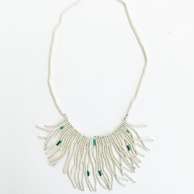 Handmade cream with green beaded fringe necklace made by Artisans in Haiti from eduacational programs providing fair wages and self-independence through generational change