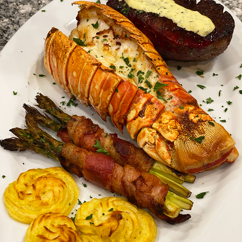 cooked lobster tail with bacon wrapped asparagus and sides
